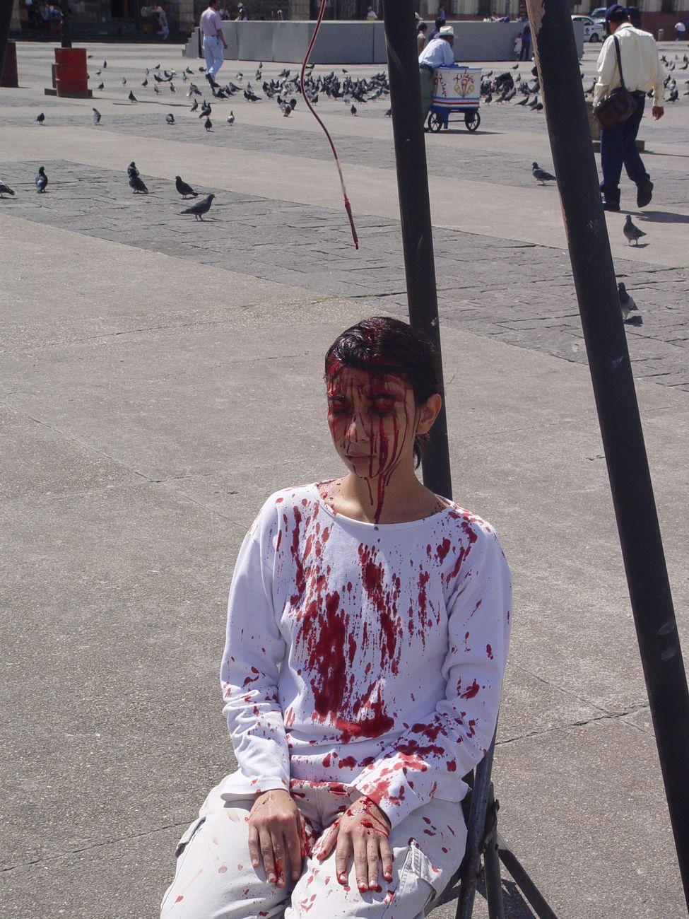 Regina José Galindo, El peso de la sangre, 2004, Plaza Central, Città del Guatemala, lambda print on forex, 75x100 cm. Photo credit Belia de Vico. Courtesy dell'artista e PrometeoGallery, Lucca Milano