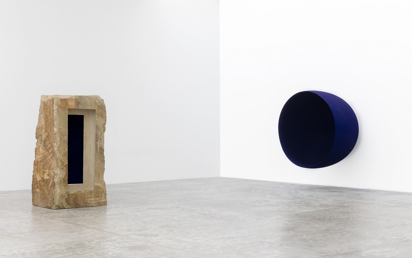 Anish Kapoor - Left: Untitled, 1992. Sandstone and pigment, 230x122x103 cm - Right: Void, 1989. Fibreglass and pigment, 200x200x152.5 cm Photograph: Michel Zabe ©Anish Kapoor. All rights reserved DACS, 2021