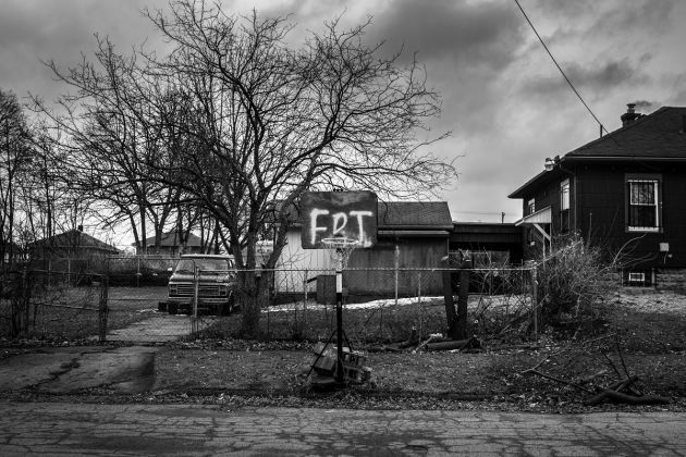 Those Who Stay Will Be Champions © Chris Donovan, Canada. A basketball net supported by cinder blocks stands beside a street in Flint, on 25 February 2020. The board reads 'FDT', an acronym based on a popular anti-Donald Trump protest song.