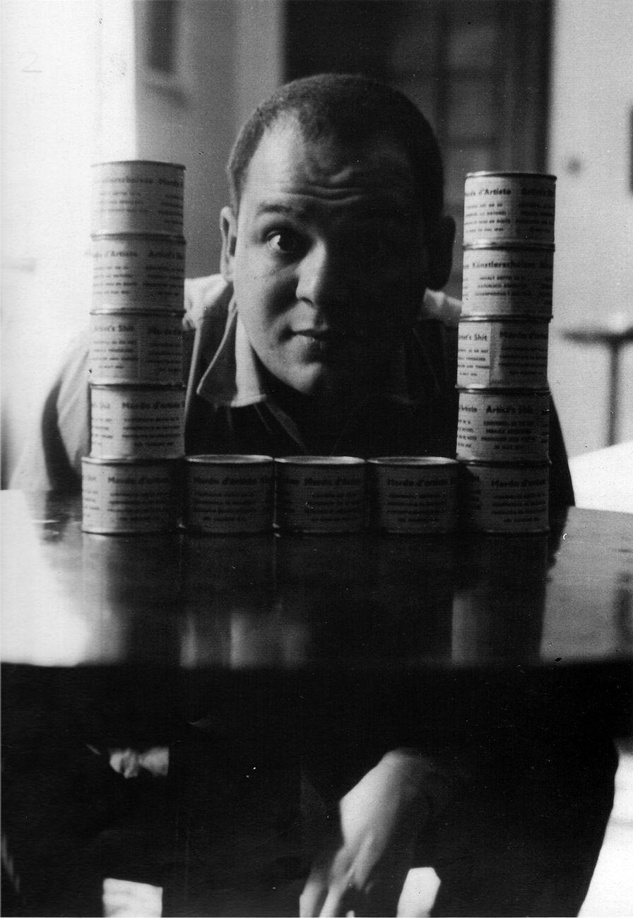 Piero Manzoni con le scatolette di Merda d'artista nella casa di Via Cernaia, Milano, 1961 © Fondazione Piero Manzoni, Milano