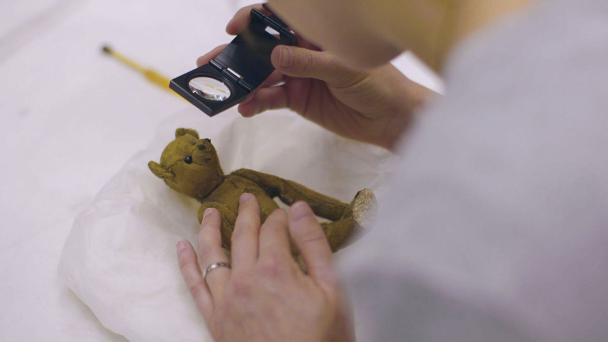 Little Tommy Tittlemouse, being inspected by conservator Nora Meller, with a magnifying glass © Blast! Films – photographer Simon Lloyd